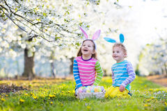 Easter egg hunt. Kids with bunny ears in spring garden. Royalty Free Stock Photography