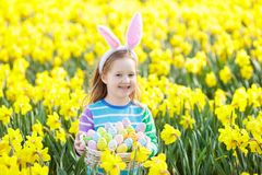 Child with bunny ears on Easter egg hunt Stock Photos