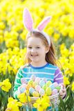 Child with bunny ears on Easter egg hunt Royalty Free Stock Photo