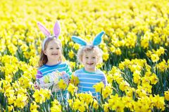 Kids with bunny ears on Easter egg hunt. Stock Photo