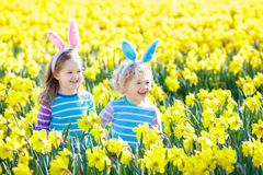 Kids with bunny ears on Easter egg hunt. Stock Photos