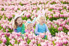 Kids on Easter egg hunt in blooming garden. Royalty Free Stock Photos