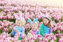 Kids on Easter egg hunt in blooming garden. Royalty Free Stock Image