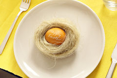 Easter egg with inscription happy easter in a nest on a plate Royalty Free Stock Photography