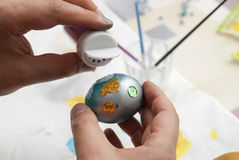 Easter Egg. Man decorating an Easter Egg with brocade Royalty Free Stock Photography