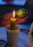 Easter egg in the master's hands above candle flame Stock Images