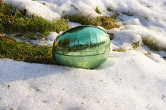 Easter-egg in melting snow Royalty Free Stock Photo