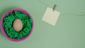 Easter egg - minimalism. Easter egg in a nest in front of green background and with a card for free text Royalty Free Stock Photography