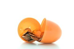 Easter Egg Money. A macro shot of some coins spilling out of a plastic Easter egg over a white background Stock Images