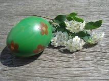 Easter egg near flower on wooden board Stock Photo