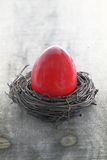 Easter egg in the nest. Red Easter egg in the nest on wooden background Stock Image