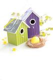 Easter egg in a nest with birdhouses and birch branches on backgr Stock Photo