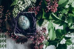 Easter egg in nest with floral and chick ornaments on rustic background with lilac flowers. top view. space for text. happy. Easter. greeting card concept stock images