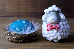 Easter egg in the nest and little sheep Stock Image