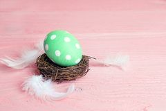 Easter egg in a nest on a pink table. Stock Images