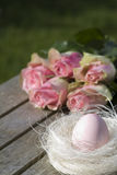 Easter egg in the nest and rose bouquet Stock Photos