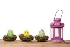 Easter egg in the nests and pink lantern. Royalty Free Stock Photography