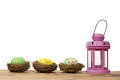 Easter egg in the nests and pink lantern on the wooden background. Stock Photos
