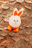 Easter egg in orange on a tree bark Stock Photography