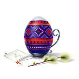 Easter egg with ornament and sprig of willow. Easter egg with beautiful multicolored blue-red ornament on vintage metal stand with handle Royalty Free Stock Images
