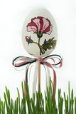 Easter egg painted with a flower with bows in the grass. Royalty Free Stock Photo
