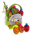 Easter egg, painted in smiling cartoon face of guy. Decorated eg. G with funny colorful hairstyle and multi-colored patterns sitting in an Easter felt basket Royalty Free Stock Photo