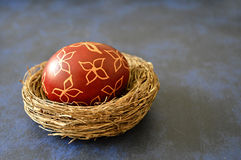Easter egg painted with wax on blue background Royalty Free Stock Image