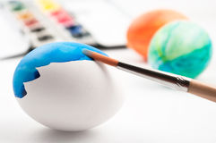 Easter egg while painting with brush. Easter egg while painting with blue color with color easter eggs and watercolor palette in background stock image