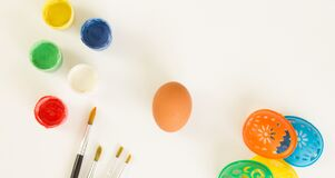 Easter egg, paints, brushes and stencils for drawing on a white background.