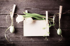 Easter egg and paper attach to rope with clothes pins and tulips Royalty Free Stock Photo