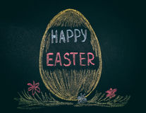 Easter egg with phrase Happy Easter on chalkboard Royalty Free Stock Image