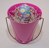 An Easter egg in a pink bucket. A single vibrantly decorated Easter egg in a pink bucket that is filled with straw royalty free stock image