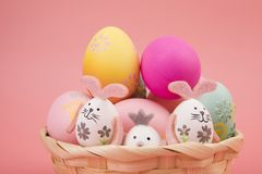 Easter egg with pink theme in basket. the egg is decorated like a cute bunny playing with another bunny, on a pink background. stock images
