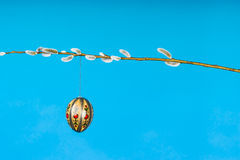 Easter egg on pussy willow twig. One easter egg hanging on pussy willow twig horizontal on blue background Royalty Free Stock Photo