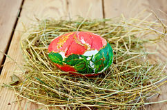 Easter egg with a red flower in the hay Royalty Free Stock Photo