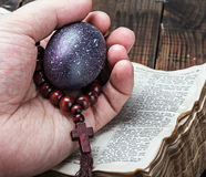 Easter egg and a rosary in a hand on an open Bible. Easter egg and a rosary in a human hand on an open Bible Stock Photo