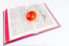 Easter egg with rosary on a holy Bible Stock Photos
