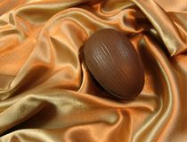 Easter egg on satin. A chocolate Easter egg on satin sheet stock images