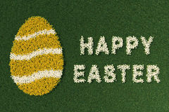 Easter egg shape and Happy Easter expression, with flowers. Easter egg shape and Happy Easter expression, with spring flowers on a green meadow Stock Photography