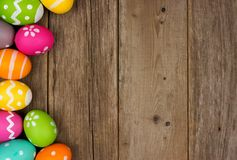 Easter egg side border against rustic wood stock photo