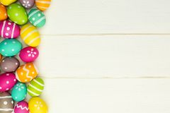 Easter egg side border against white wood. Colorful Easter egg side border against a white wood background Royalty Free Stock Image