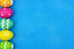Easter egg side border over blue burlap background Royalty Free Stock Photography