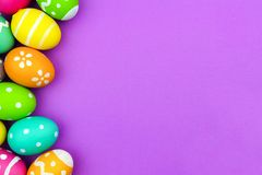 Easter egg side border over purple paper background Royalty Free Stock Images
