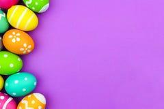 Easter egg side border over purple paper background Royalty Free Stock Images