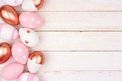 Easter egg side border. Rose gold, pink and white on white wood. royalty free stock photo