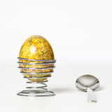 Easter egg. And spoon. Yellow, spotted, multicolored egg, metal holder Stock Image