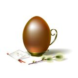 Easter egg with sprig of willow. Easter egg dark gold on vintage metal stand with handle Stock Photos