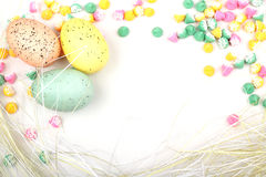Easter Egg Straw Framed Background. A pastel background framed border of soft colored Mini Meltie candies, straw and speckled colored Easter eggs. Copy Space stock images