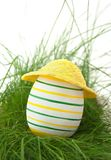 Easter egg in straw yellow hat in green grass Stock Photo