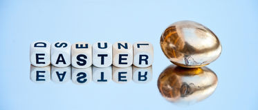Easter egg. Text 'Easter ' in upper case black letters on small white cubes next to a golden egg isolated on bright reflective background Stock Photography